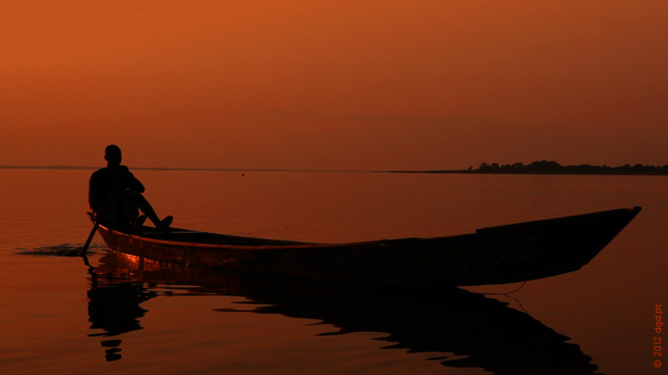 fisherman in wooden canoe boat paddling toward shore during sunset on lake volta in ghana africa